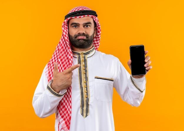 Arabische zakenman in traditionele slijtage die smartphone toont die met vinger ernaar richt kijkt die verward over oranje muur staat