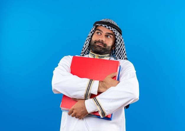 Arabische zakenman in traditionele slijtage die twee omslagen houdt die verward opzij kijken en zich over blauwe muur bevinden