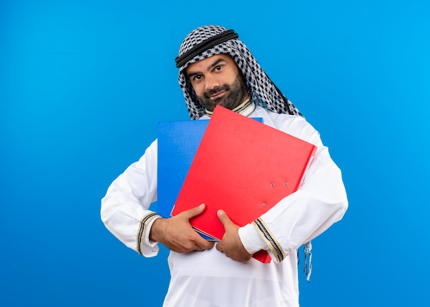 Arabische zakenman in traditionele slijtage die twee omslagen met glimlach op gezicht houdt die zich over blauwe muur bevinden