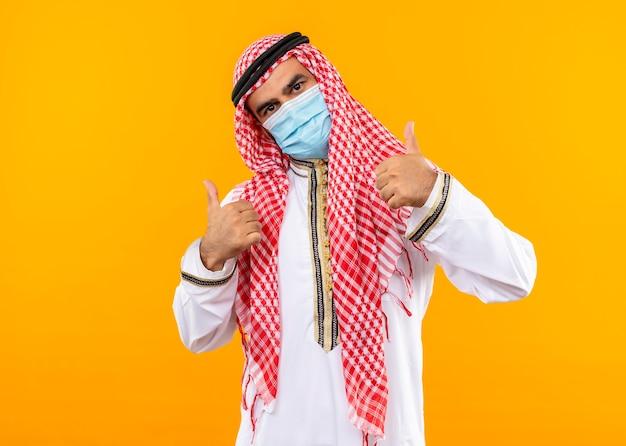 Arabische zakenman in traditionele slijtage en gezichts beschermend masker met zelfverzekerde uitdrukking die duimen toont die zich over oranje muur bevinden