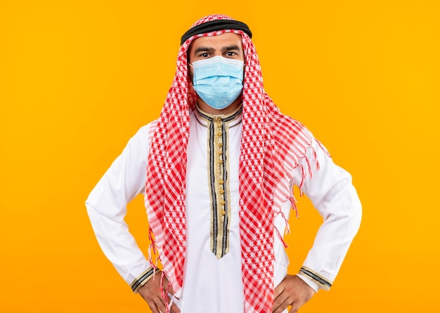 Arabische zakenman in traditionele slijtage en gezichts beschermend masker met zelfverzekerde uitdrukking die zich over oranje muur bevindt