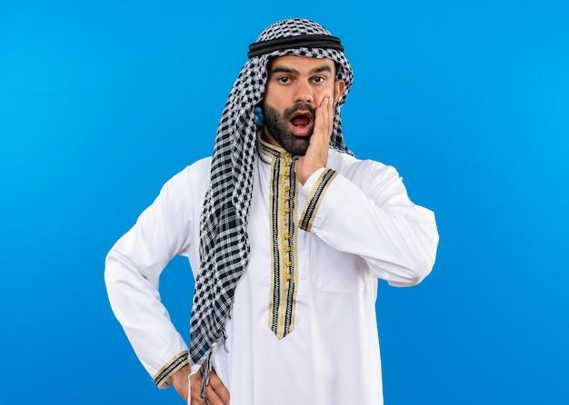 Arabische zakenman in traditionele slijtage geschokt aanraken met arm zijn gezicht staande over blauwe muur