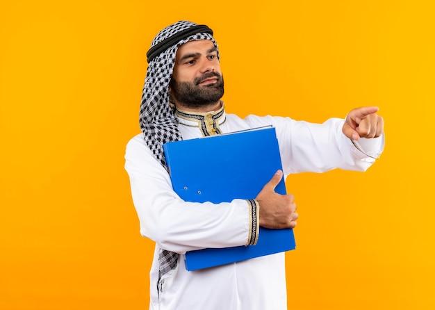 Arabische zakenman in traditionele slijtage met blauwe map opzij kijkend wijzend met de vinger naar de kant staande over oranje muur