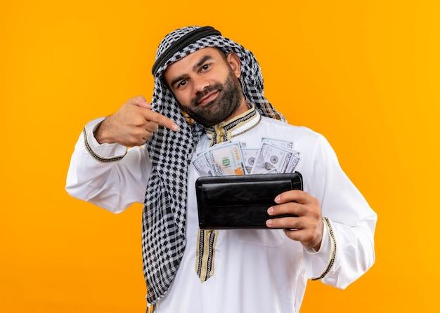 Arabische zakenman in traditionele slijtage met portemonnee met contant geld glimlachend zelfverzekerd wijzend met vinger naar contant geld staande over oranje muur
