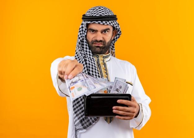 Arabische zakenman in traditionele slijtage met portemonnee met contant geld met ernstig gezicht staande over oranje muur