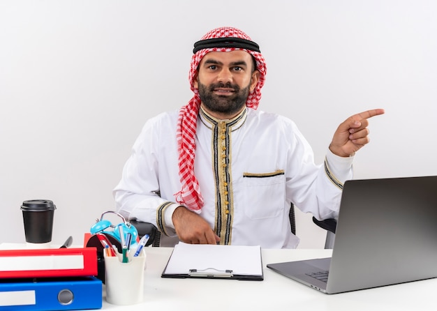 Arabische zakenman in traditionele slijtage werken met laptop computer wijzend met vinger naar de zijkant op zoek zelfverzekerd zittend aan de tafel in kantoor