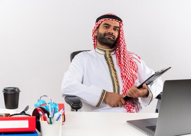 Arabische zakenman in traditionele slijtage zittend aan de tafel met laptop computer klembord op zoek naar vertrouwen werken in kantoor