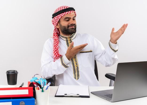 Arabische zakenman in traditionele slijtage zittend aan de tafel met laptop computerpointing met armen ti de kant op zoek zelfverzekerd werken op kantoor
