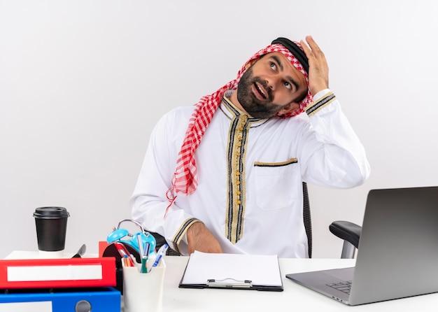 Arabische zakenman in traditionele slijtage zittend aan de tafel met laptop op zoek verward met twijfels werken in kantoor