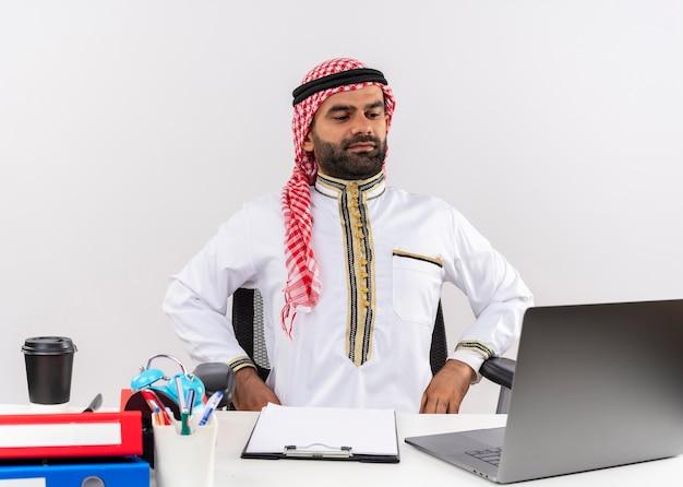 Arabische zakenman in traditionele slijtage zittend aan de tafel met laptop opzij kijken met zelfverzekerde uitdrukking werken in kantoor