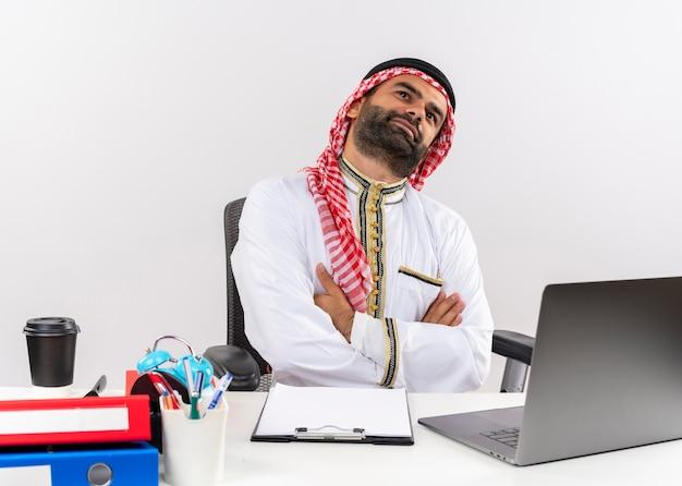 Arabische zakenman in traditionele slijtage zittend aan de tafel met laptop opzoeken met dromerige gezichtsuitdrukking werken in kantoor