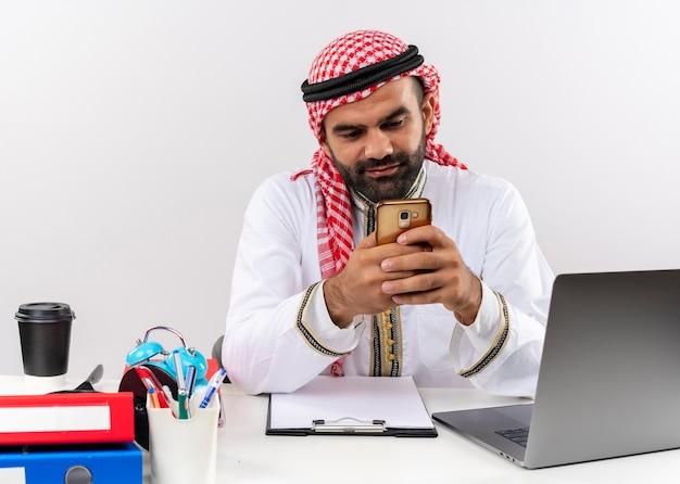 Arabische zakenman in traditionele slijtage zittend aan de tafel met laptopcomputer smartphone sms bericht werken op kantoor te houden