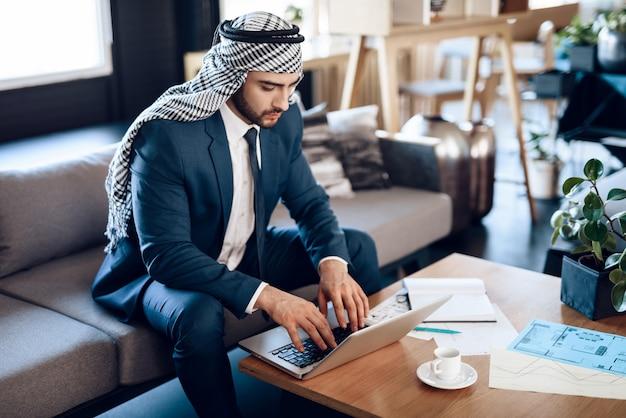 Arabische zakenman op lapton op laag bij hotelruimte