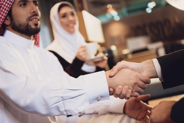 Arabische zakenman schudt handen met partner.