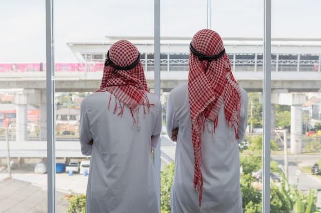 Arabische zakenman twee die zich kijkend aan de grote projectbouw achteruitgaan