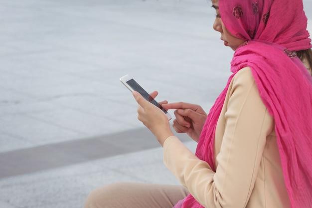 Arabische zakenvrouw messaging op een mobiele telefoon in de stad