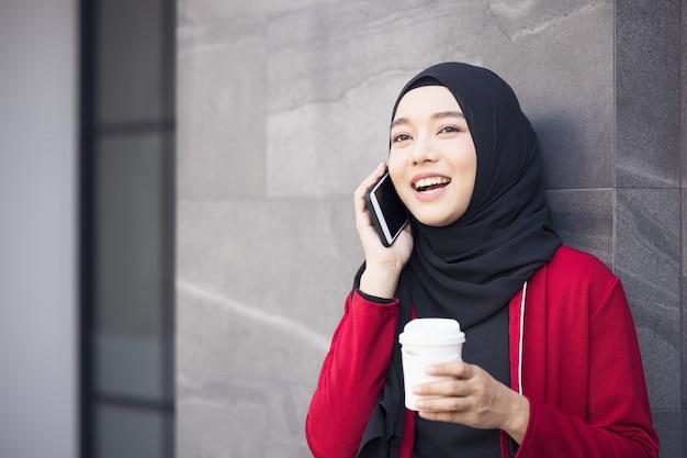 Arabische zakenvrouwen in hijab die een kopje koffie op straat houden en een mobiele telefoon vasthouden