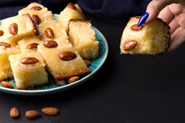 Arabische zoete basbus-taart in stukjes gesneden op een zwarte achtergrond