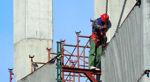 Arbeid die op de bouwplaats werkt en vinyl en staal plaatst om het gebouw en de blauwe lucht te bedekken.