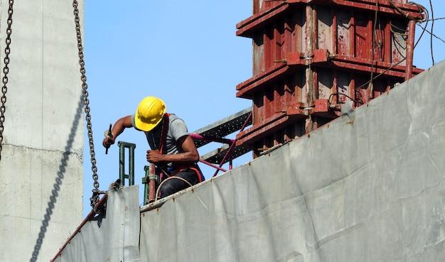 Arbeid man aan het werk op de bouwplaats met helm en safty apparatuur en het gebouw bedekken met grijze kleur vinyl en blauwe lucht.