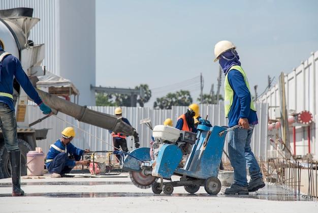 Arbeid of bouwvakker met behulp van de beton van de werktuigmachinesnijder voor de bestrating van de plasweg