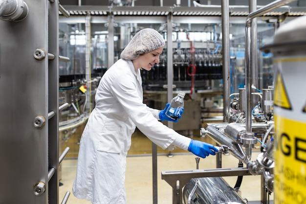 Arbeider bij bottelarij die sapkwaliteit controleert.