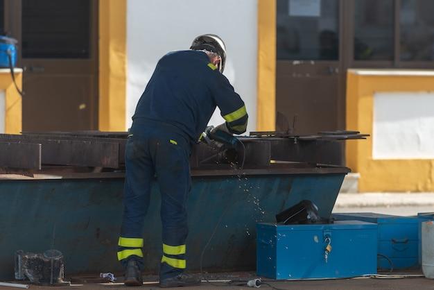 Arbeider die aan schip werkt dat werf herstelt