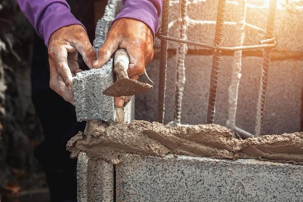 Arbeider die bakstenen in bouwwerf installeren