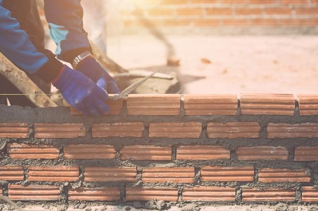 Arbeider die bakstenen muur installeren in proces van woningbouw