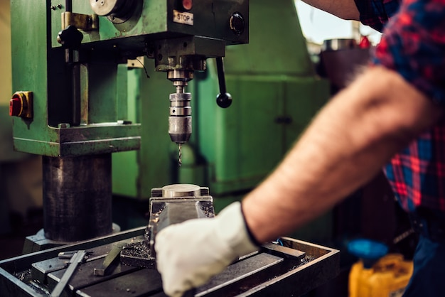 Arbeider die boorpers in de industriële fabriek met behulp van