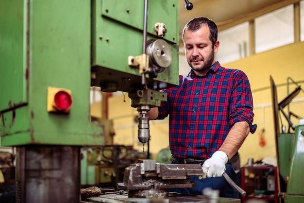 Arbeider die boorpers in fabriek met behulp van