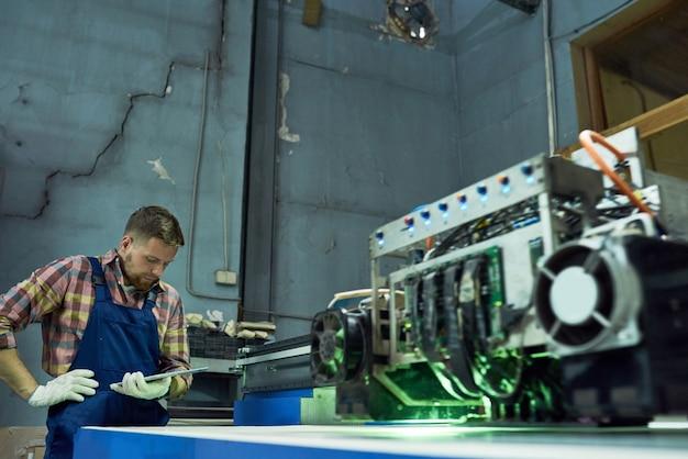 Arbeider die cnc materiaal in fabriek bedient