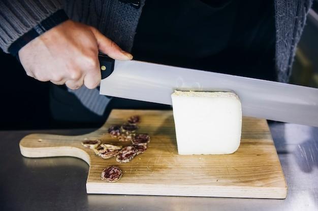 Arbeider die de kaas snijdt