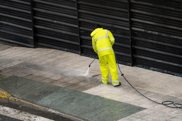Arbeider die de stoep met water onder druk schoonmaakt. onderhouds- of reinigingsconcept