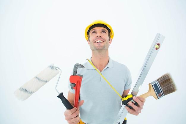 Arbeider die divers materiaal over witte achtergrond houdt
