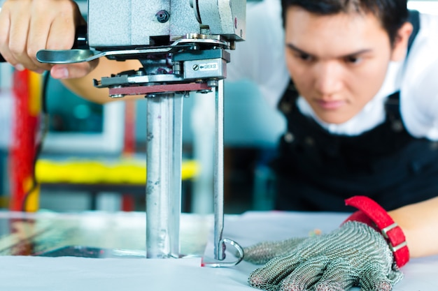 Arbeider die een machine in chinese fabriek gebruikt