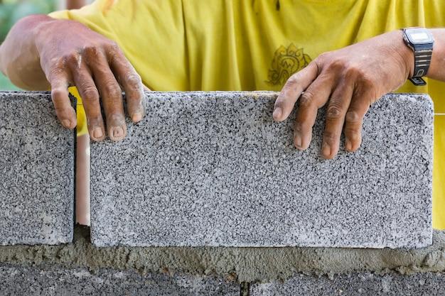 Arbeider die een muur met bakstenen bouwt