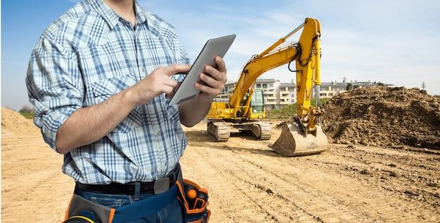 Arbeider die een tablet in een constuctionplaats gebruikt