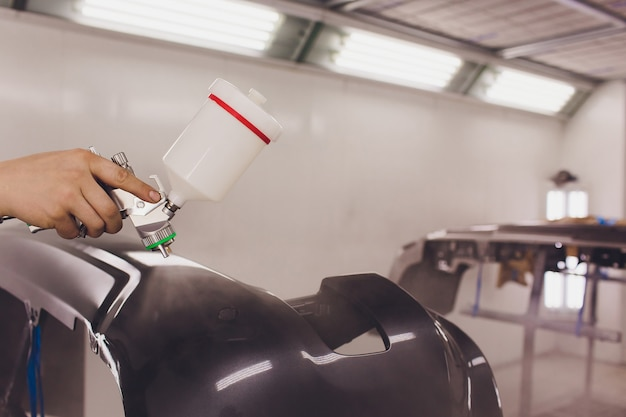 Arbeider die een zwarte lege delen van een auto in speciale garage schildert, kostuum en beschermende kleding draagt.