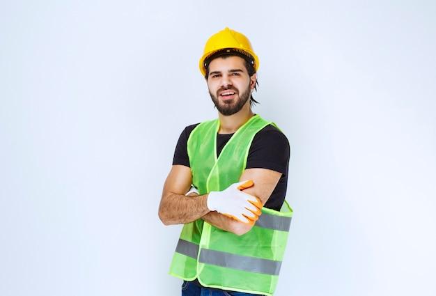 Arbeider die gele helm en workshophandschoenen draagt.
