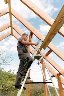 Arbeider die het dak van het huis bouwt