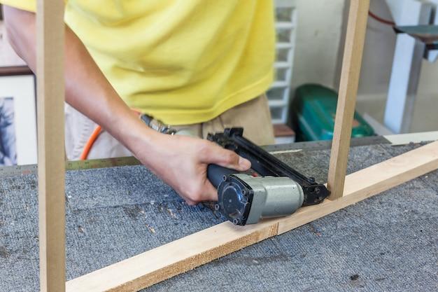 Arbeider die luchtspijkermachine gebruiken die spijker in hoek van houten frame schieten