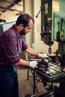 Arbeider die metaaldossier in een fabriek met behulp van
