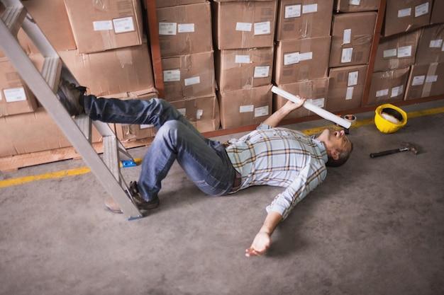 Arbeider die op de vloer in pakhuis ligt