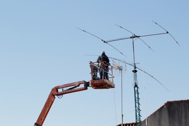 Arbeider die op telescopische lift een antenne met blauwe hemel herstelt. communicatie onderhoud