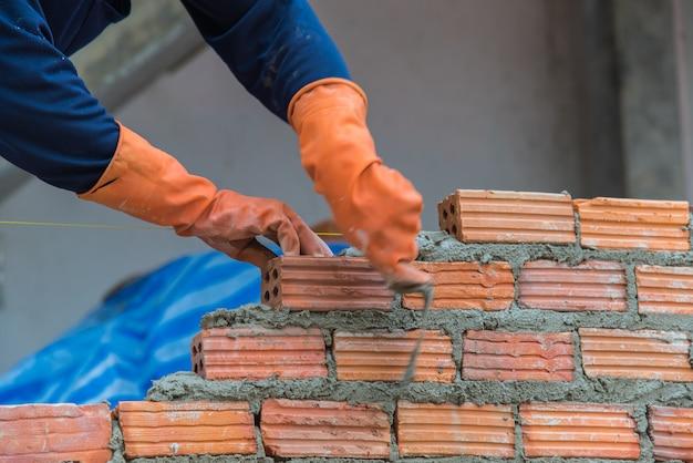 Arbeider die rode baksteen installeren bij bouwwerf