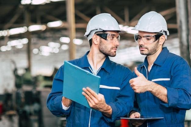 Arbeider die samenwerken bekijkend een gezicht van de jongensvriend. homomannen worden verliefd op vrienden aan het werk in de fabriek.