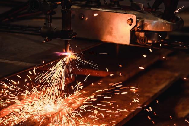 Arbeider die staalplaat met acetyleenlassen snijbrander snijdt
