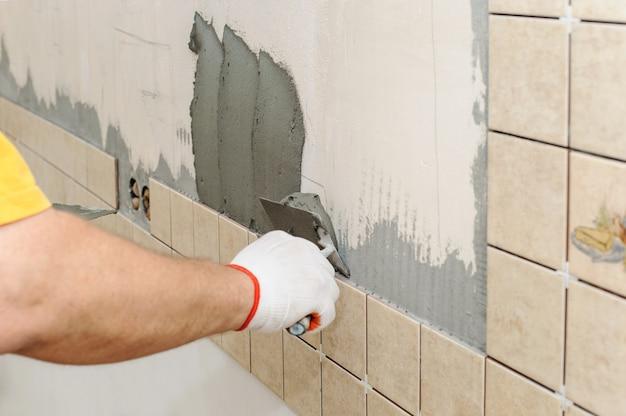 Arbeider die tegels op de muur in de keuken instiling.