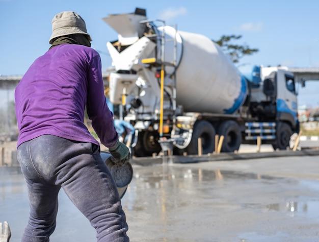 Arbeider die voor het nivelleren van concrete bestrating voor grondvloeren werkt bij bouwwerf.